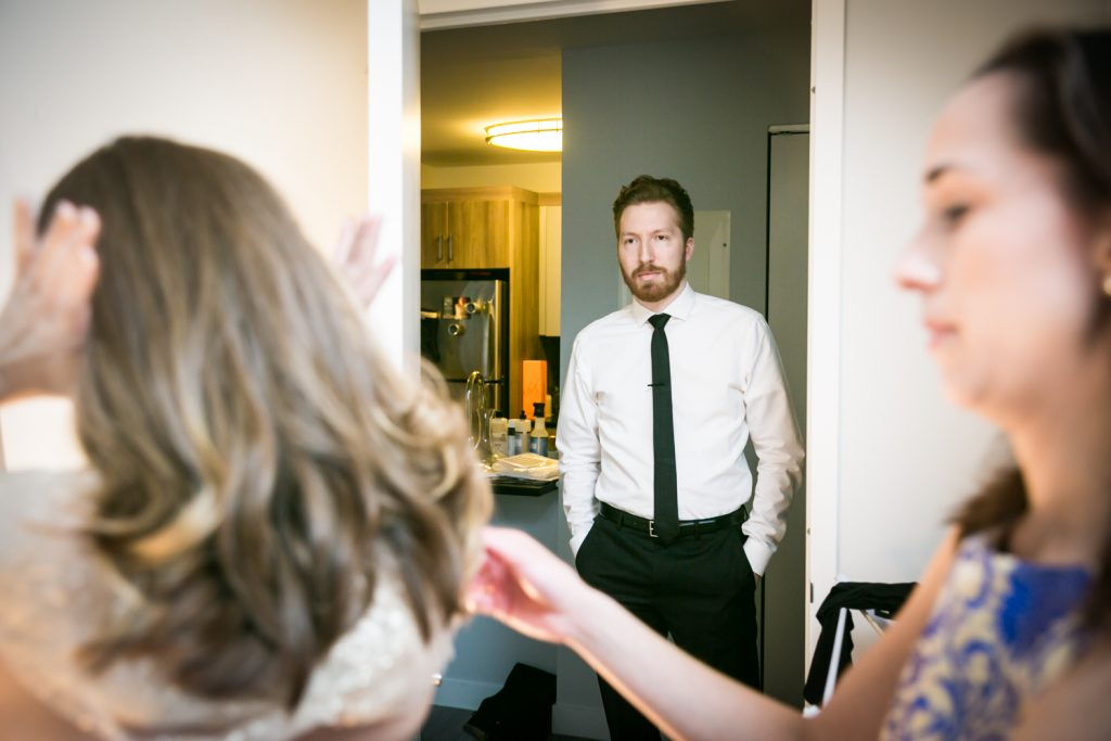 Groom watching bride get ready before wedding
