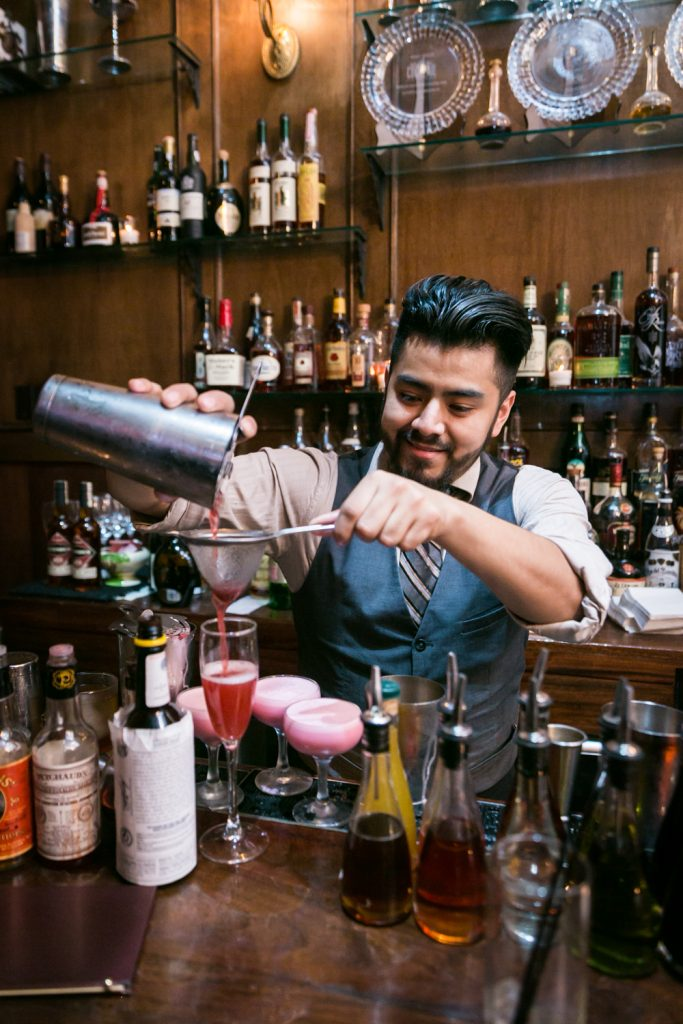 Bartender making cocktail at bar at a Clover Club wedding