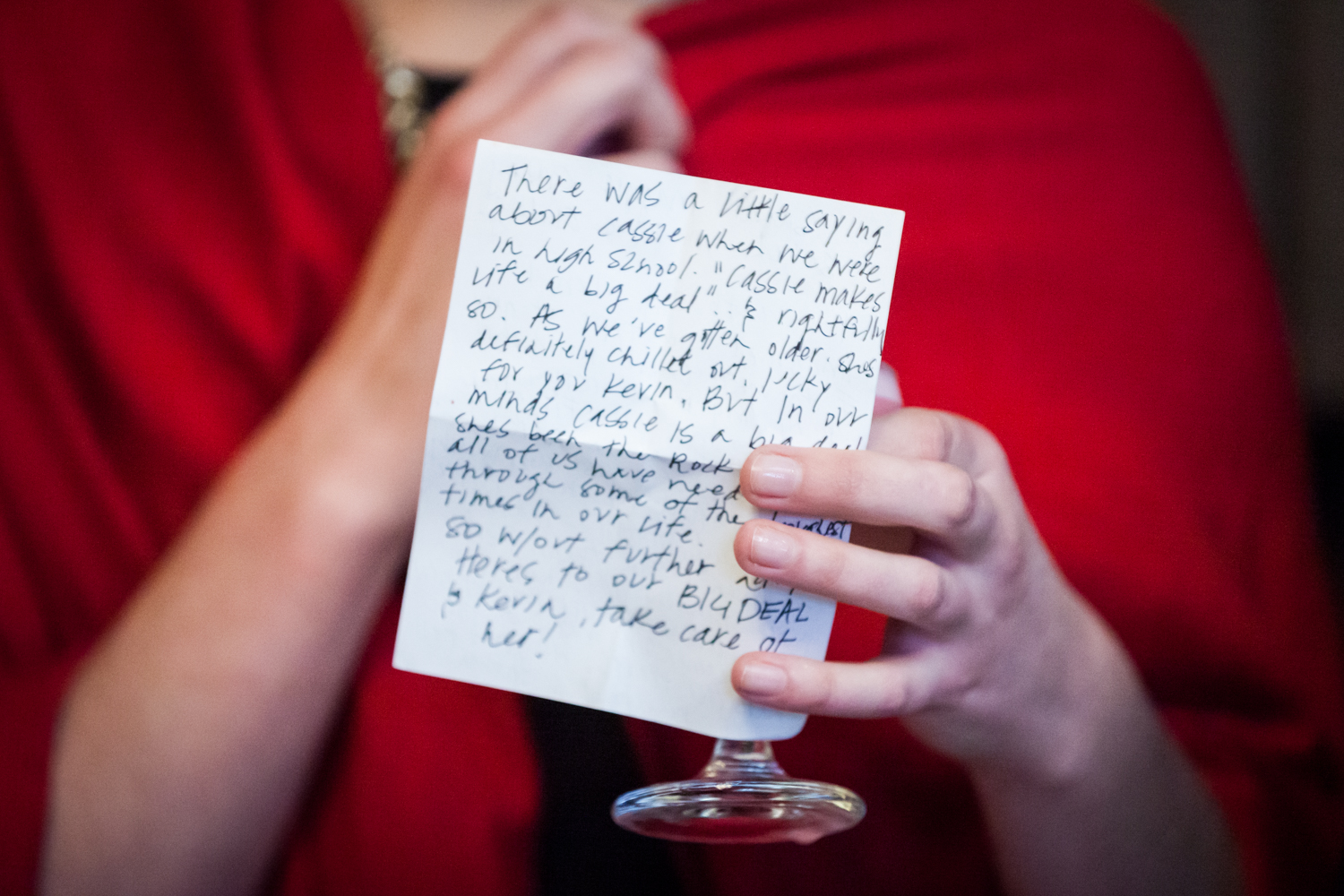 Close up on guest holding drink and note with writing