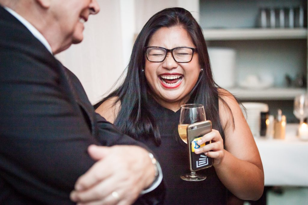 Female guest holding wine glass and laughing at wedding reception