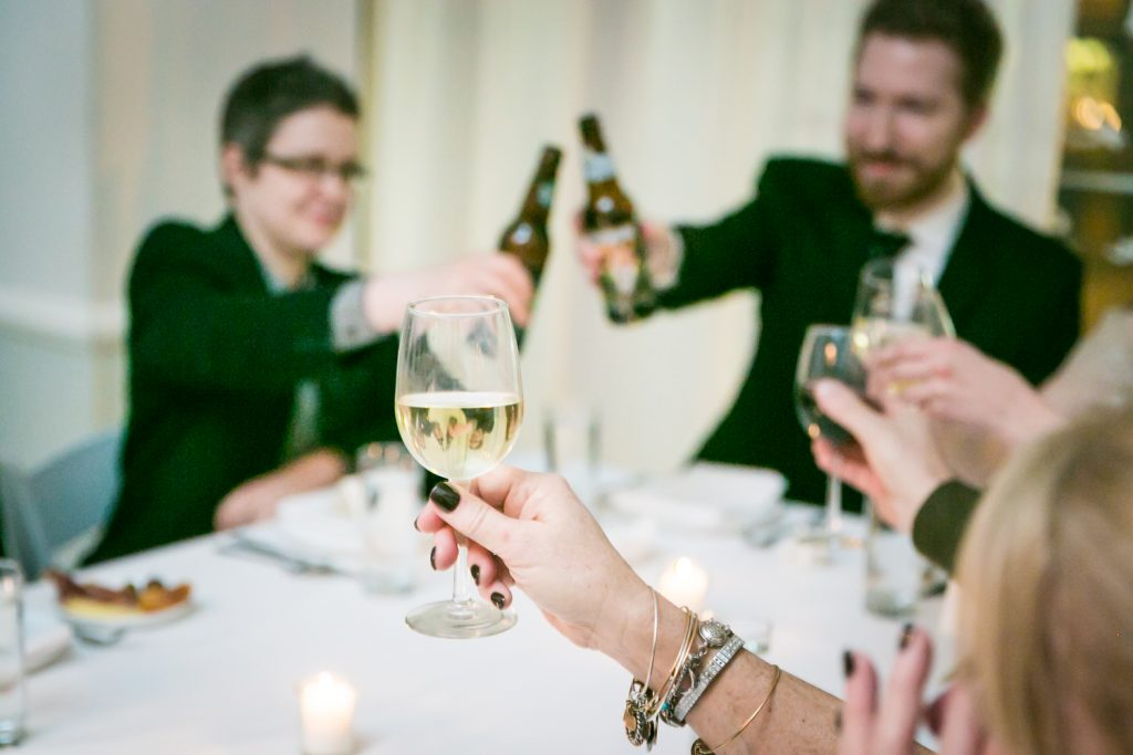 Close up on guest holding up wine glass during toasts