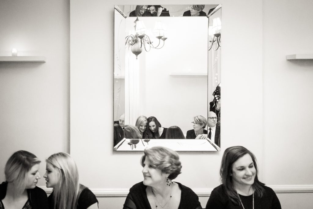 Black and white photo of guests talking and reflected in mirror