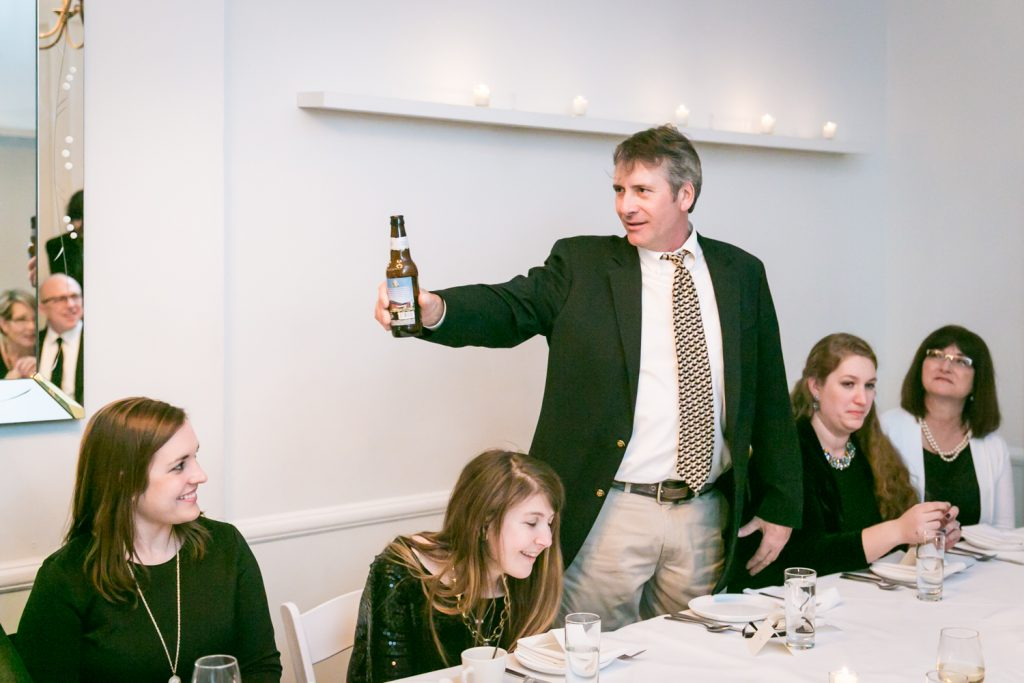 Guest holding up beer bottle during speeches at a Maison May wedding reception