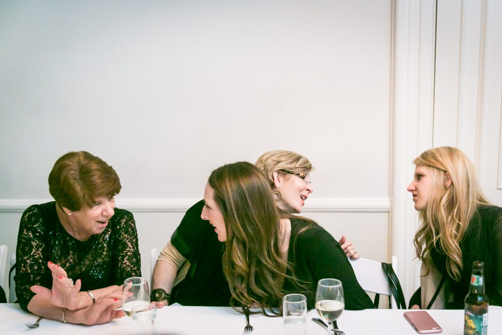 Four female guests talking at table during Maison May wedding reception