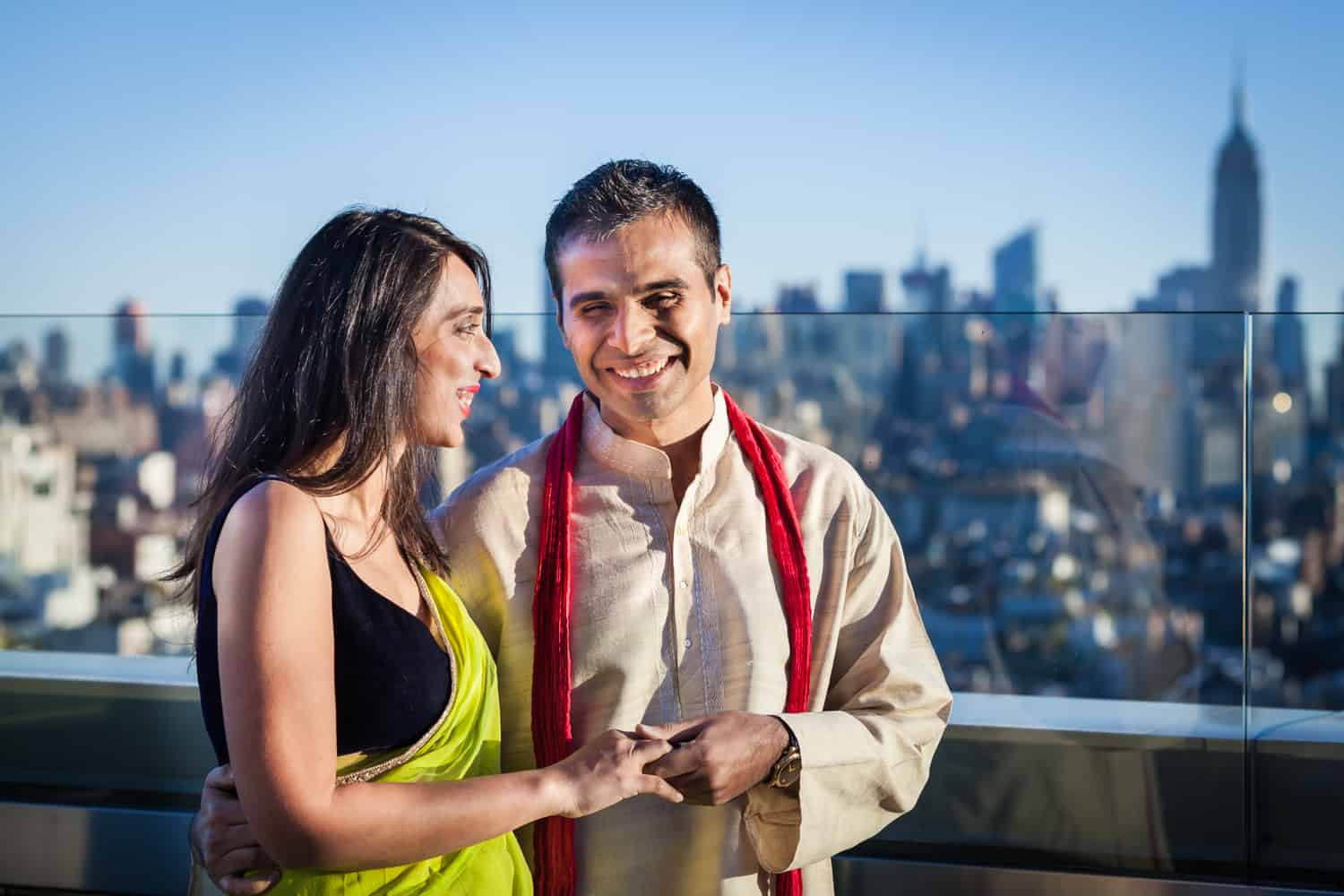 Engaged couple on rooftop wearing traditional Indian attire for an article entitled,' How I get clients comfortable in front of the camera'