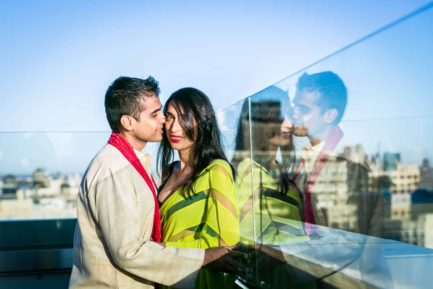 Engaged couple on rooftop wearing traditional Indian attire with reflection in glass wall