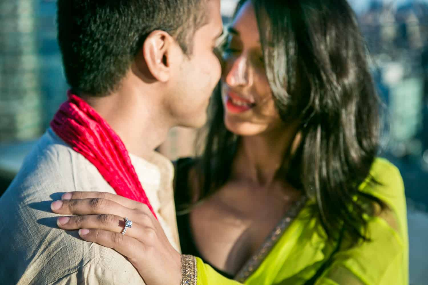 Woman's hand on man's shoulder wearing engagement ring and traditional Indian attire