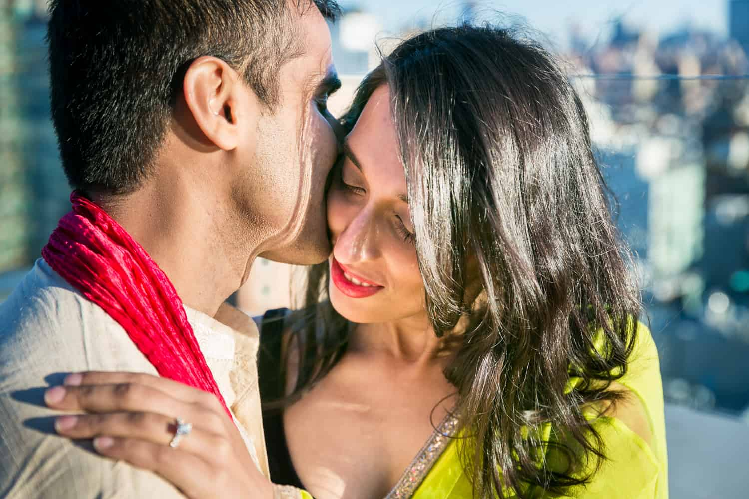 Couple wearing traditional Indian attire and man kissing woman on side of head