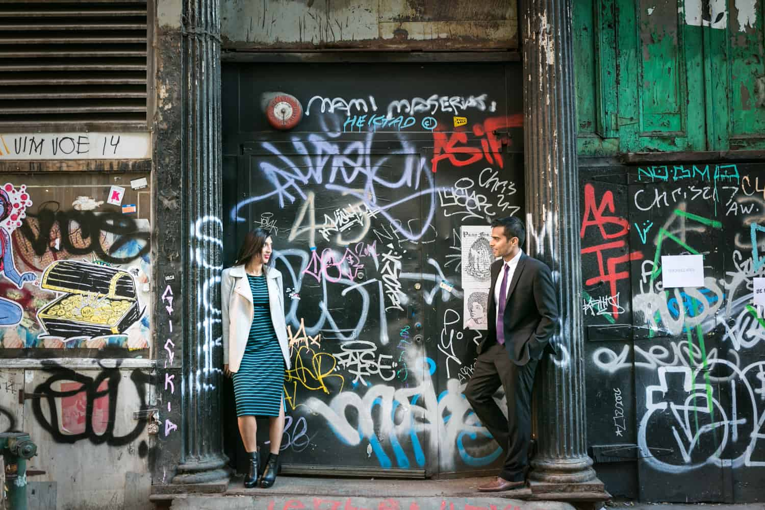 Couple leaning separately against columns of graffiti-covered wall for an article entitled,' How I get clients comfortable in front of the camera'