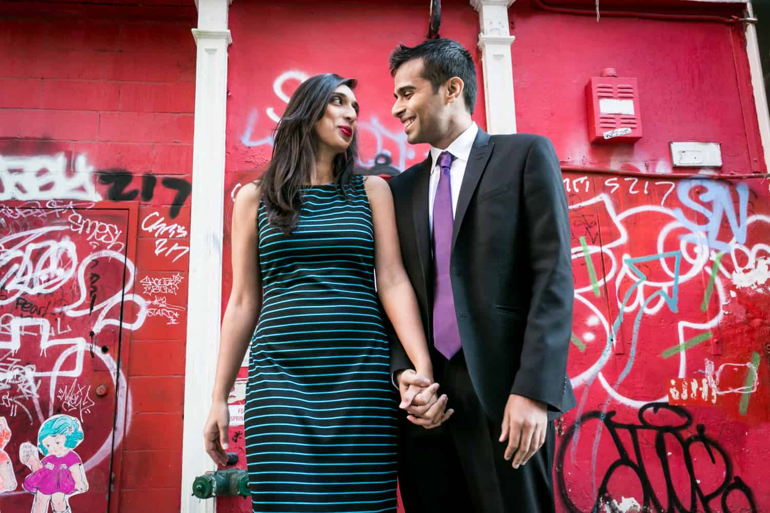 Couple holding hands in front of red graffiti wall in Tribeca