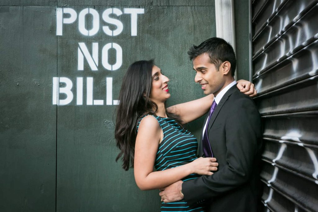 Couple hugging in front of 'post no bills' wall in Tribeca