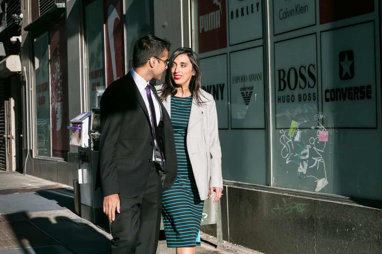 Couple walking down Tribeca sidewalk during engagement shoot