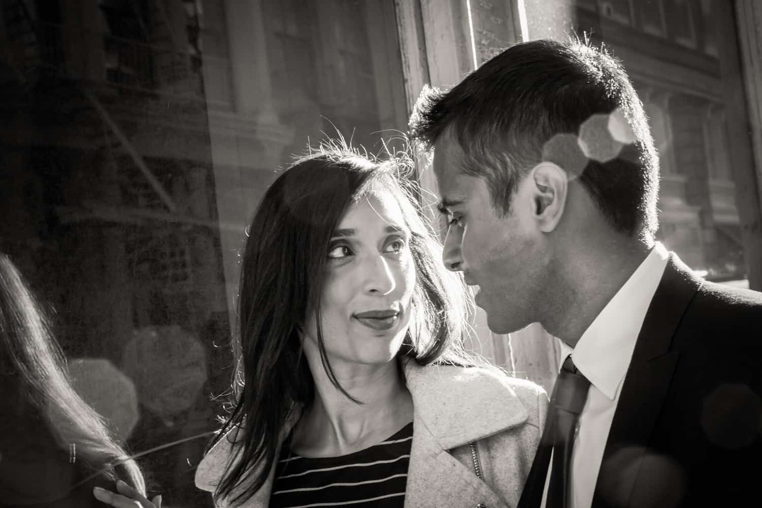 Black and white photo of engaged couple walking down street in Tribeca