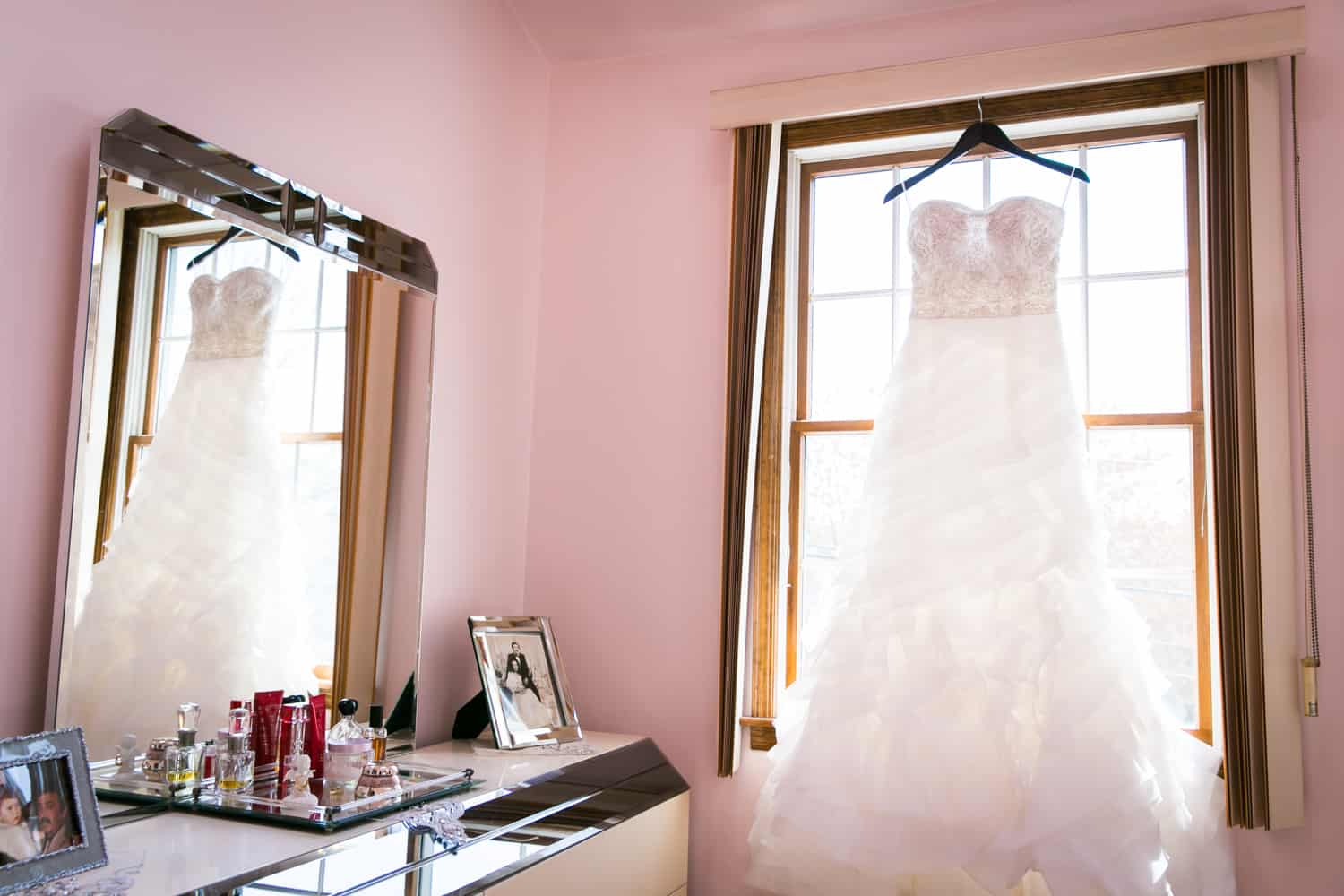 Wedding dress hanging in window and reflected in mirror for an article called 'Do you need a second photographer?'