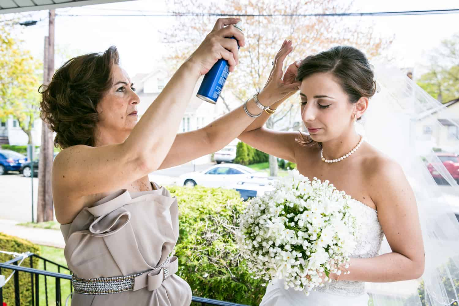 Mother spraying bride's hair with hairspray