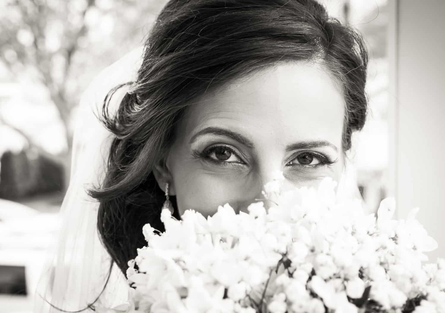 Black and white photo of bride looking over bouquet
