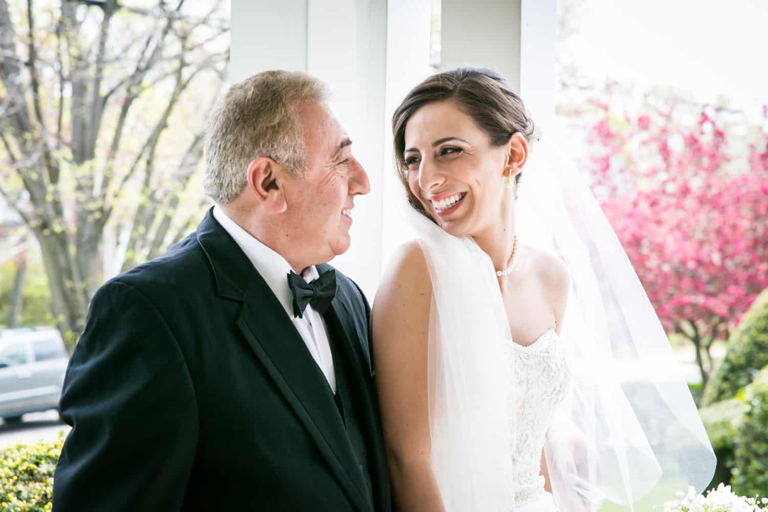 Bride and father laughing on porch for an article called 'Do you need a second photographer?'