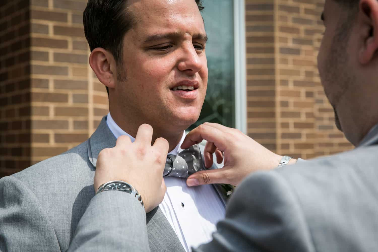 Man's hands adjusting bowtie of groom for an article called 'Do you need a second photographer?'