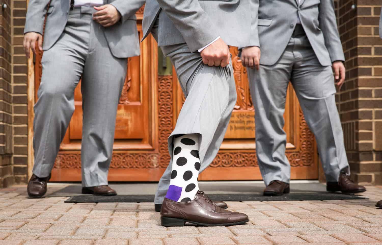 Close up of groomsmen showing off fancy socks