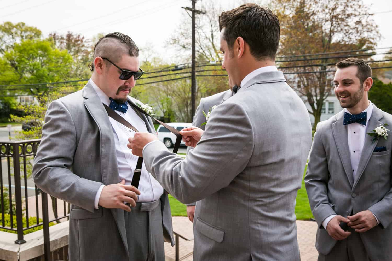 Groom snapping suspenders of groomsman wearing sunglasses