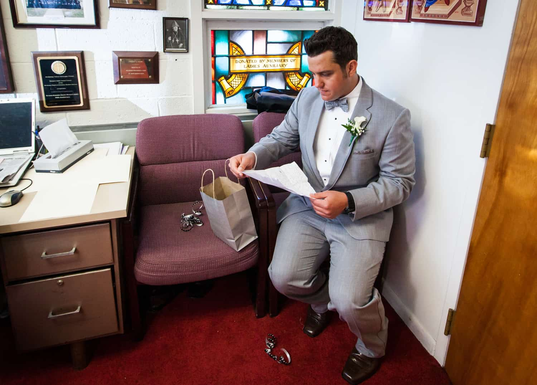 Groom sitting in church reading letter