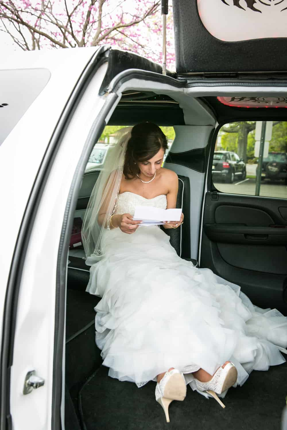 Bride sitting in limo reading letter