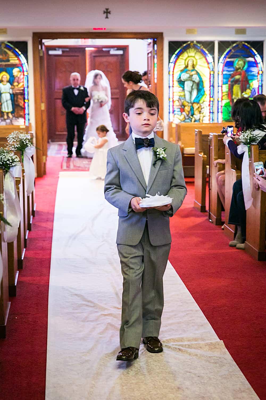 Ring bearer walking down aisle in Eastern Orthodox wedding ceremony