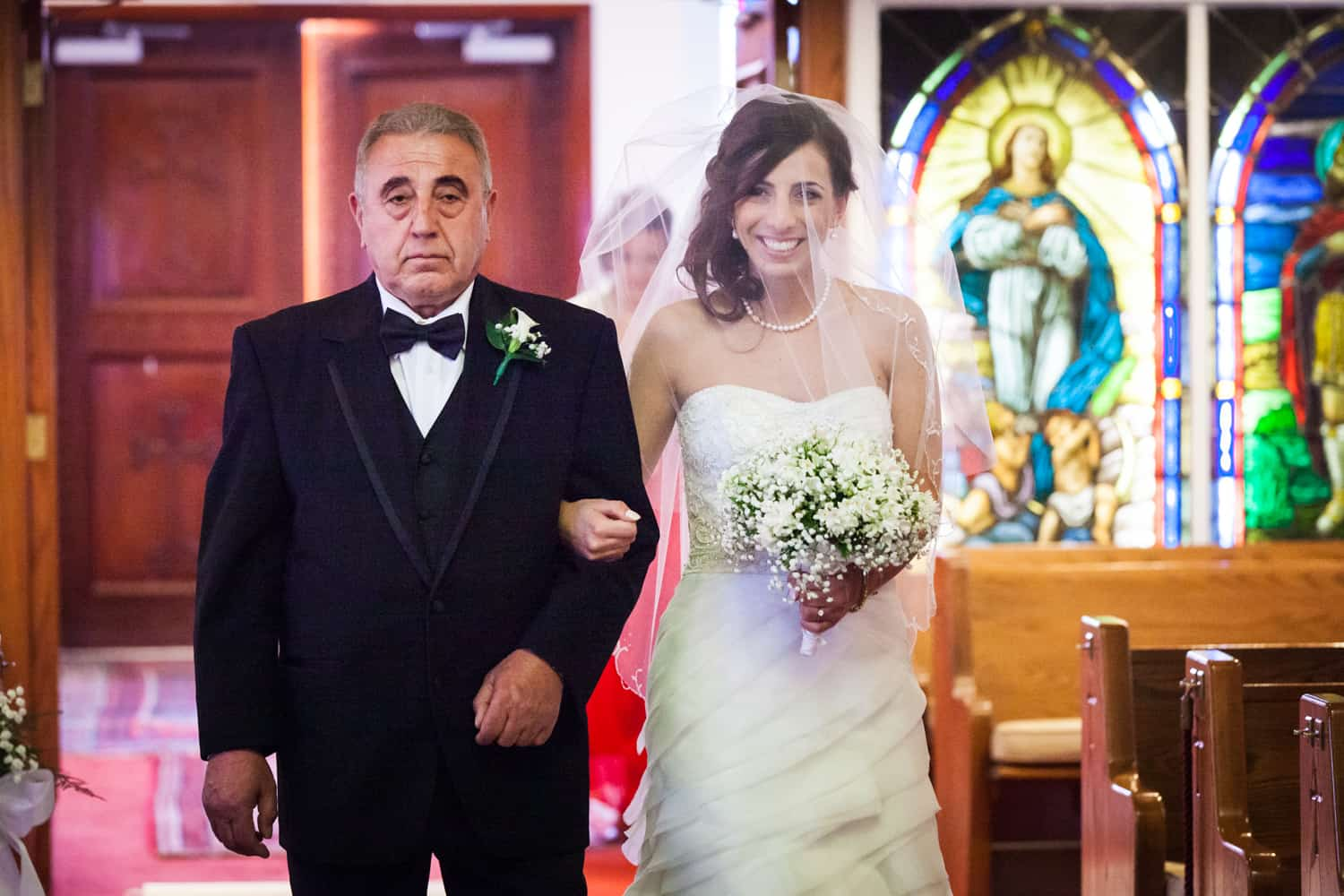 Bride and father walking down aisle in Eastern Orthodox wedding ceremony