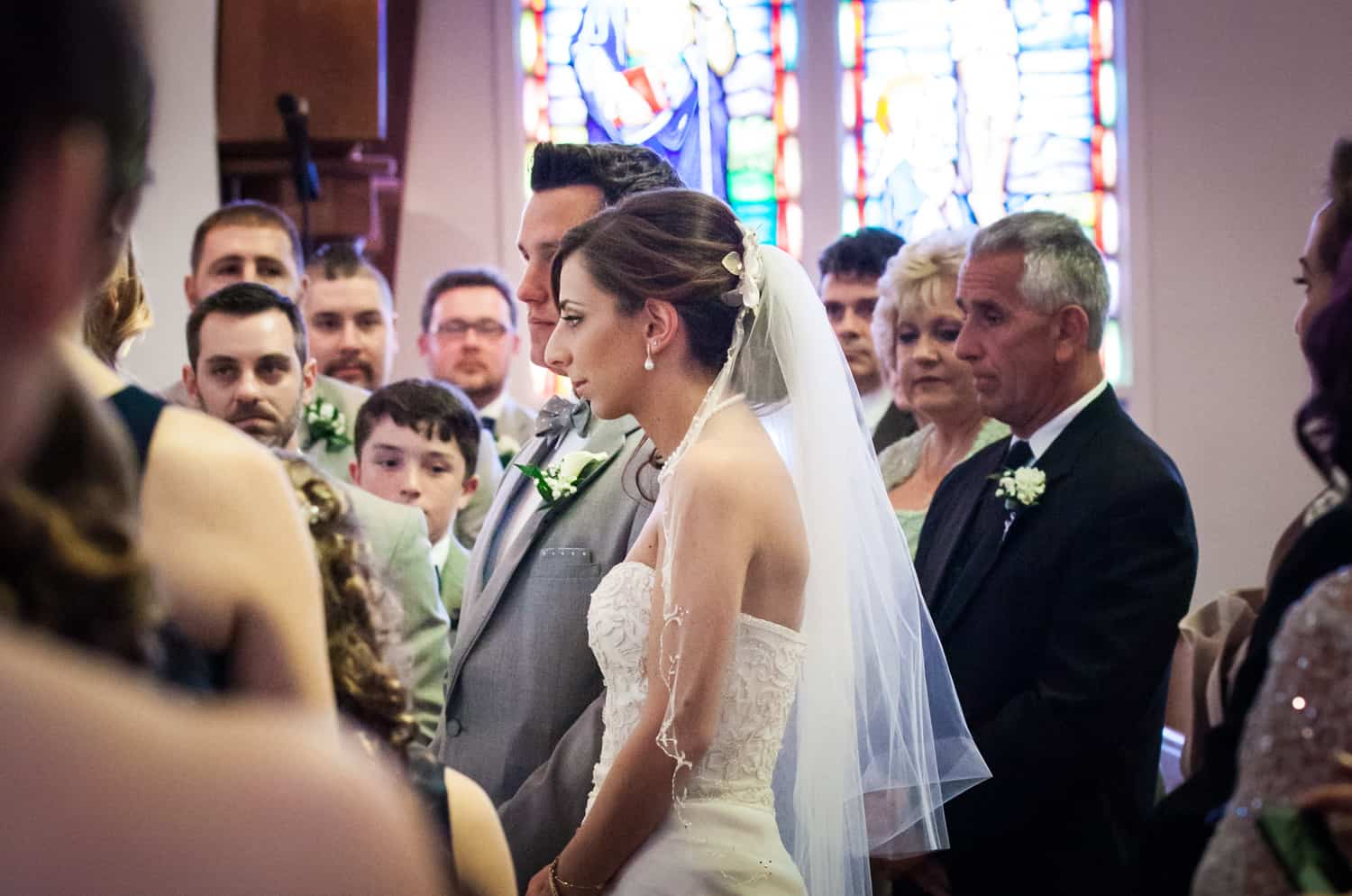 Bride and groom in front of guests in Eastern Orthodox wedding ceremony