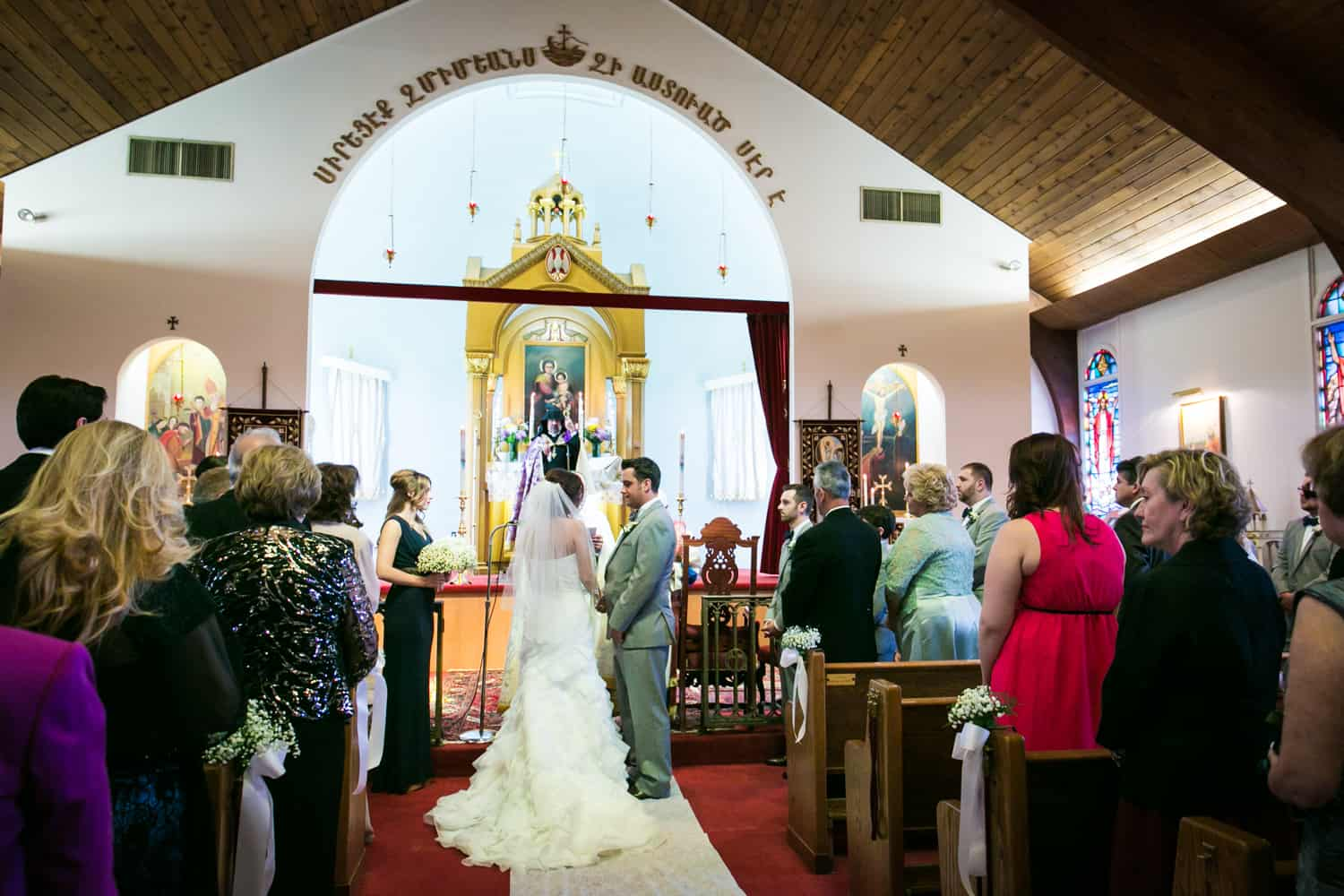 Bride and groom exchanging vows in Eastern Orthodox wedding ceremony