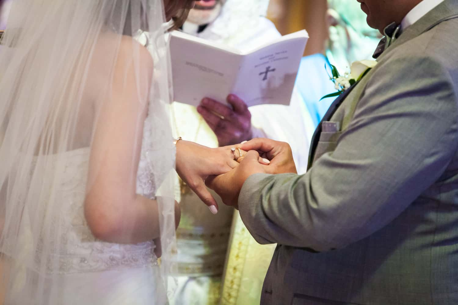 Groom putting ring on bride's finger in Eastern Orthodox wedding ceremony