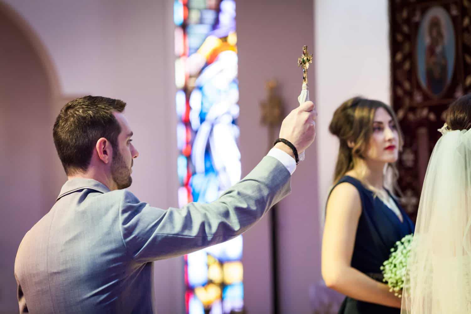 Best man holding up cross in Eastern Orthodox wedding ceremony