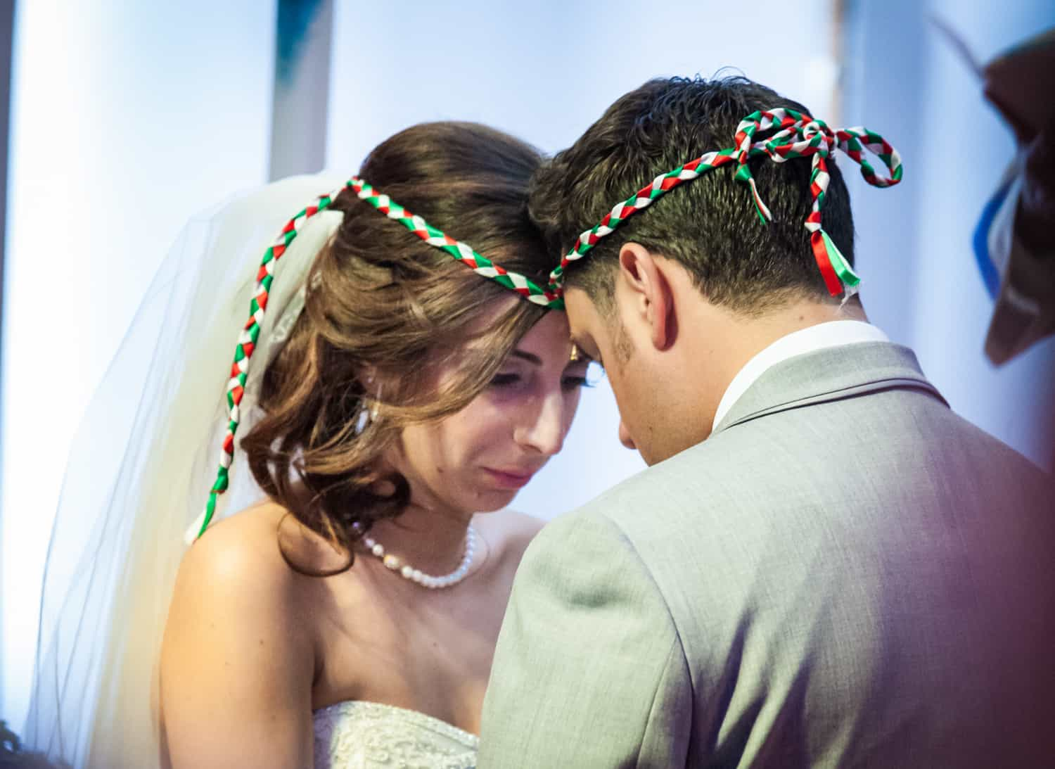 Bride and groom touching foreheads in Eastern Orthodox wedding ceremony