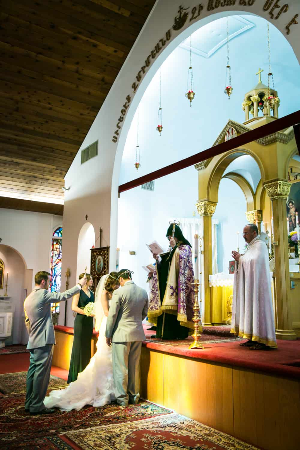 Bride and groom being blessed in Eastern Orthodox wedding ceremony