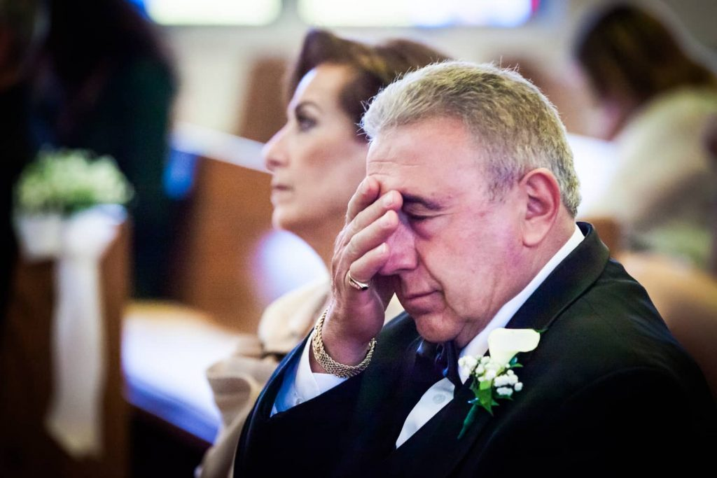 Father wiping away tears in Eastern Orthodox wedding ceremony