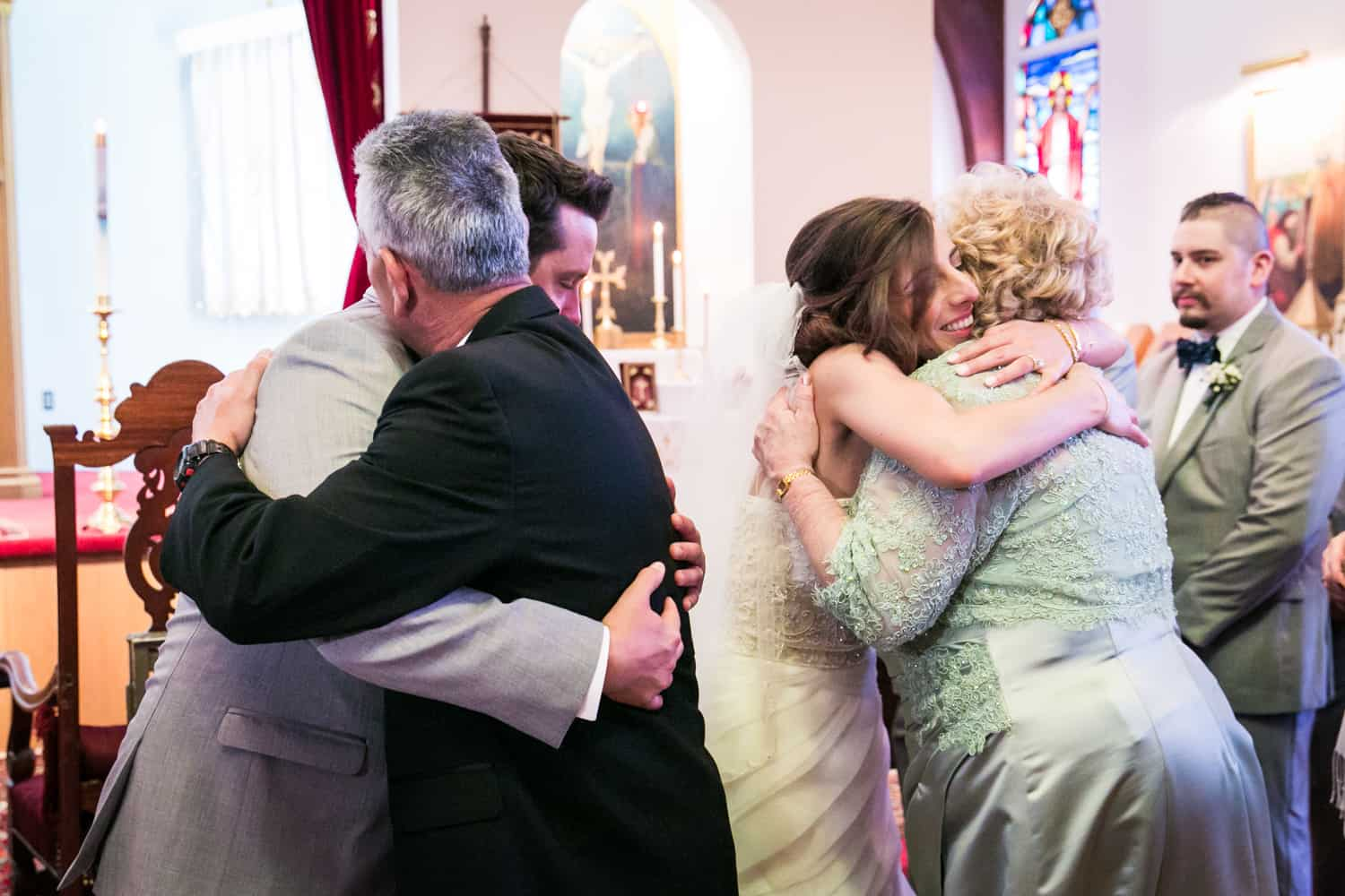 Bride and groom hugging guests after Eastern Orthodox wedding ceremony