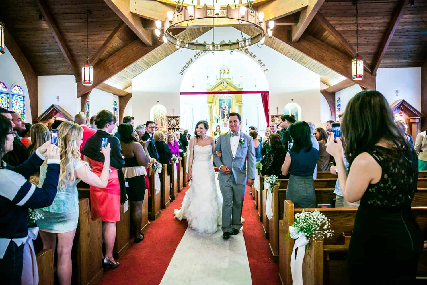 Bride and groom walking down aisle after ceremony for an article called 'Do you need a second photographer?'