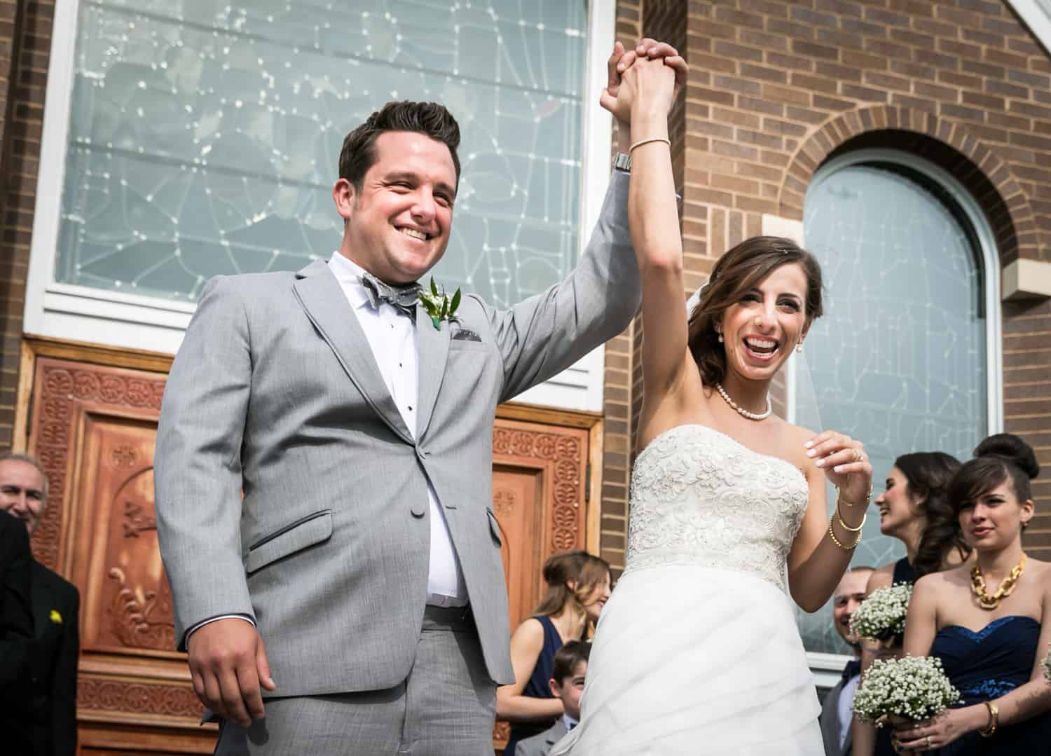 Bride and groom holding hands in the air for an article called 'Do you need a second photographer?'