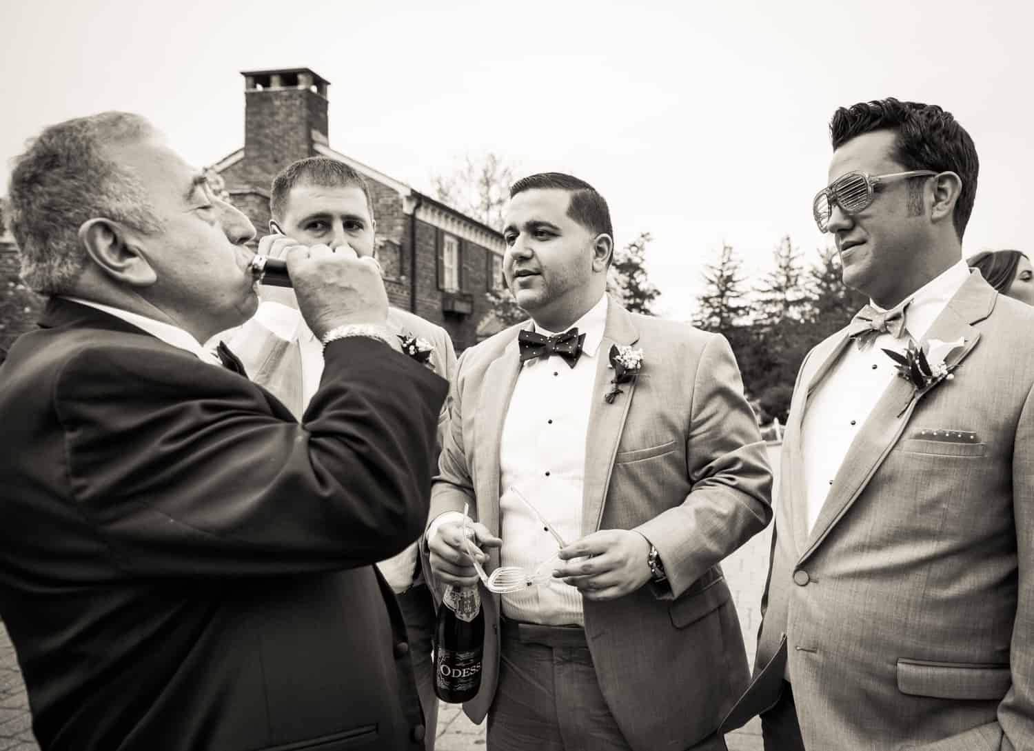 Black and white photo of groomsmen watching father of bride drink from flask