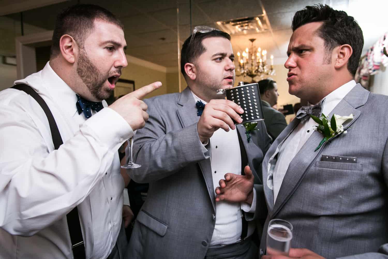 Groomsmen pointing at groom in bridal suite