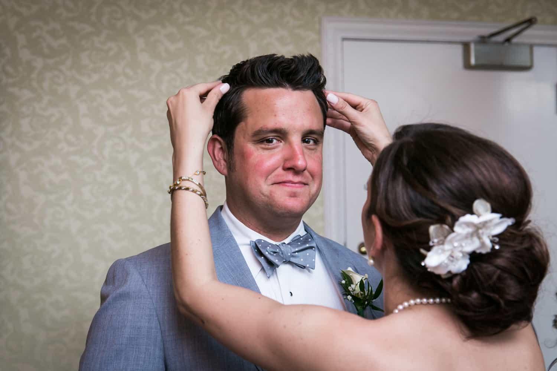 Bride fixing hair of groom in bridal suite