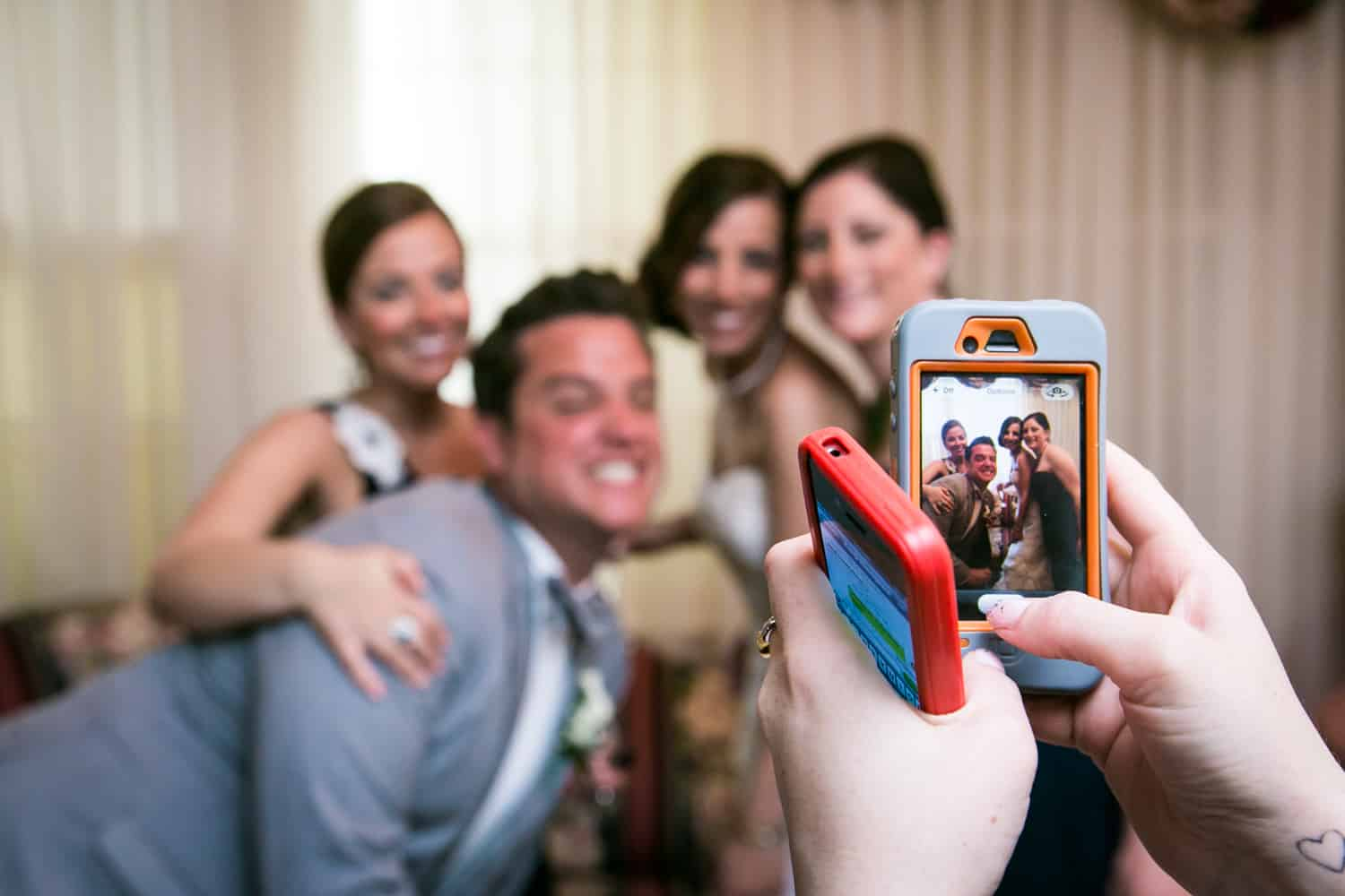 Hands taking photo of bridal party with cell phone