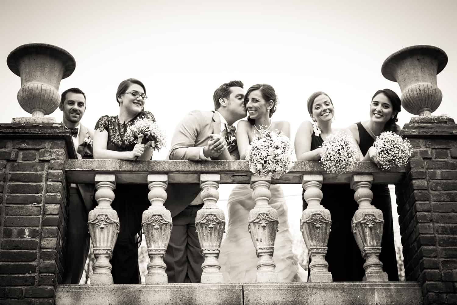 Black and white photo of bridal party leaning over railing and groom kissing bride