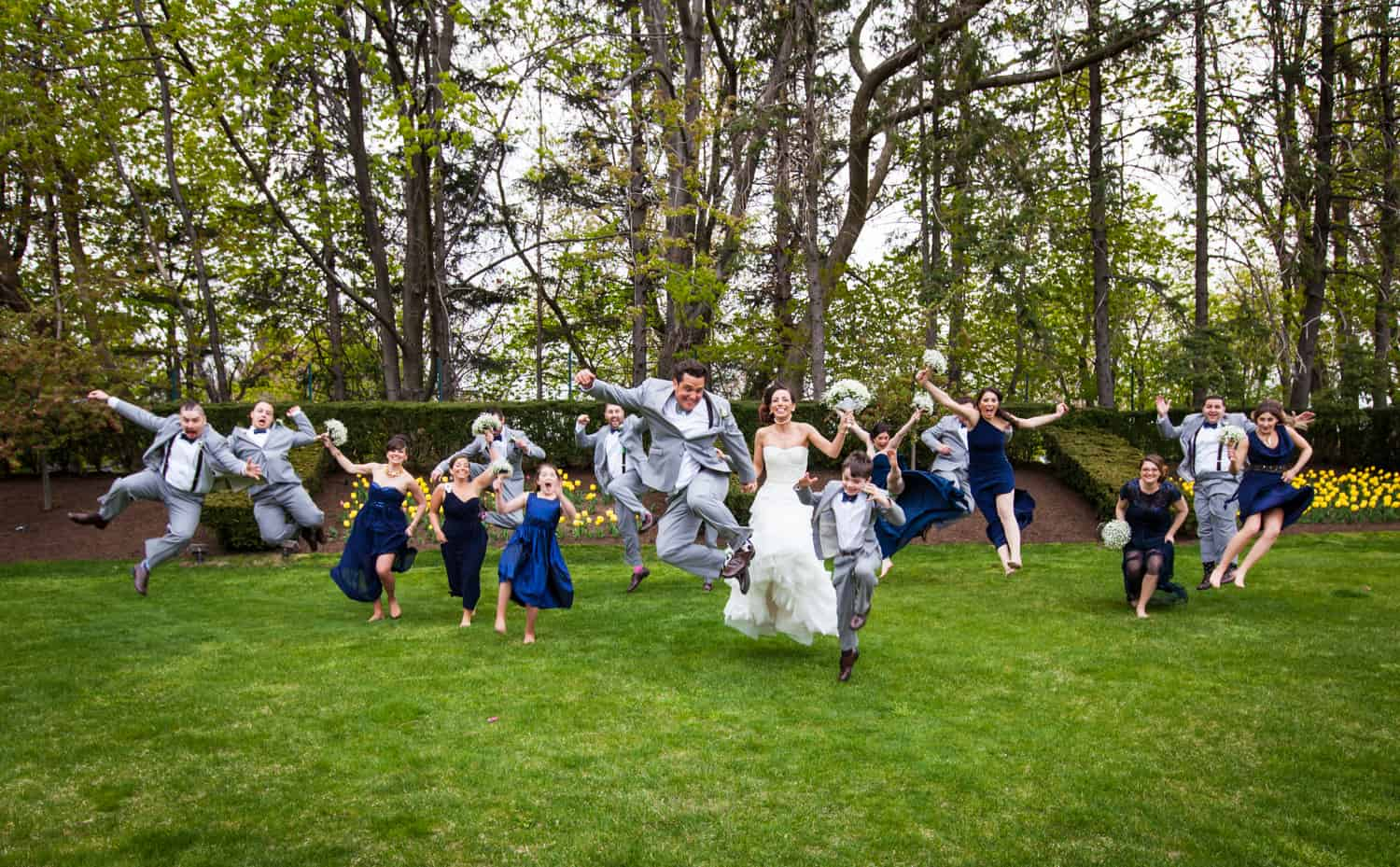 Bridal party jumping on grass for an article called 'Do you need a second photographer?'