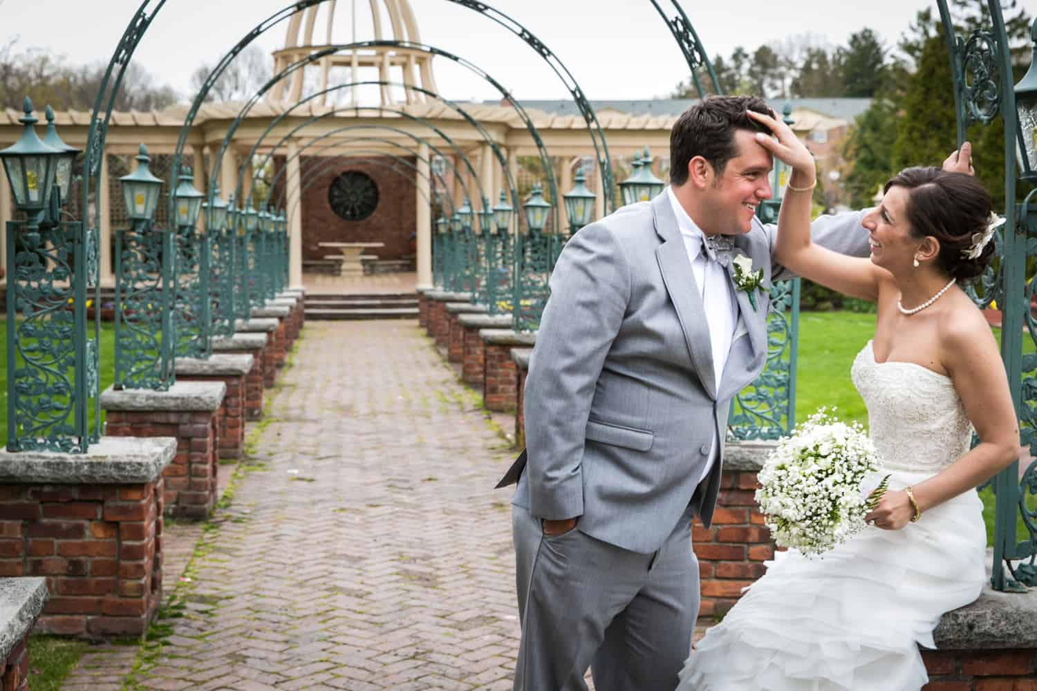 Bride fixing hair of groom on patio of the Manor