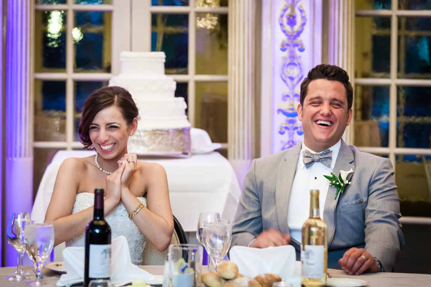 Bride and groom at sweetheart table laughing during speeches