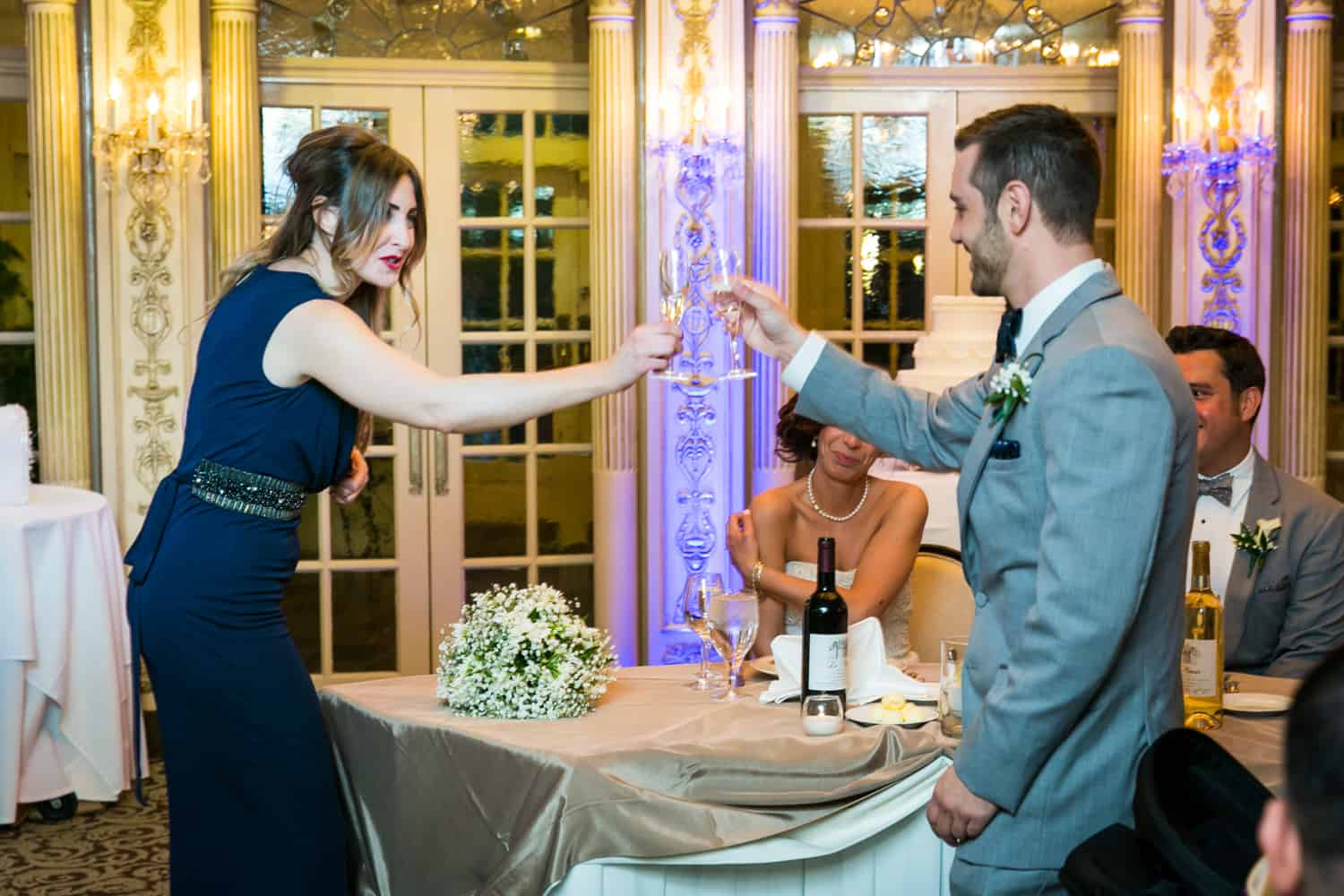 Best man and maid of honor toasting champagne glasses