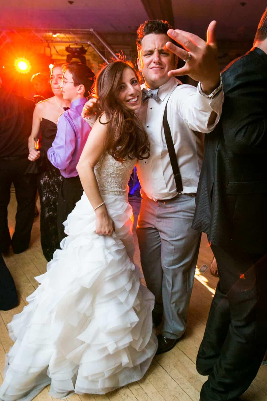 Bride and groom gesturing to camera during Manor wedding reception