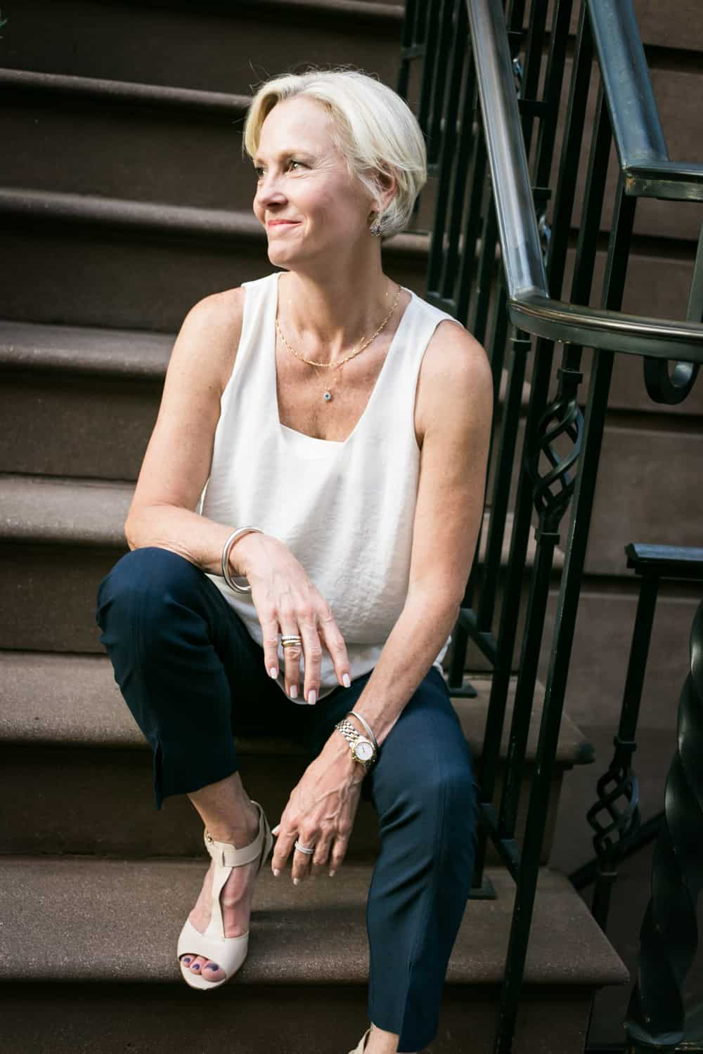 Older woman wearing white sleeveless top sitting on steps