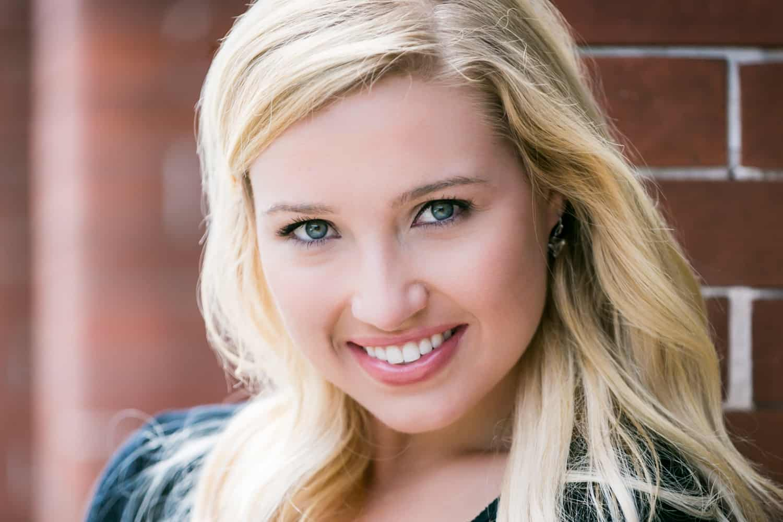 Smiling blond actress wearing blue shirt